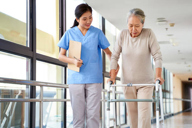 young asian physical therapist working with senior patient stock photo
