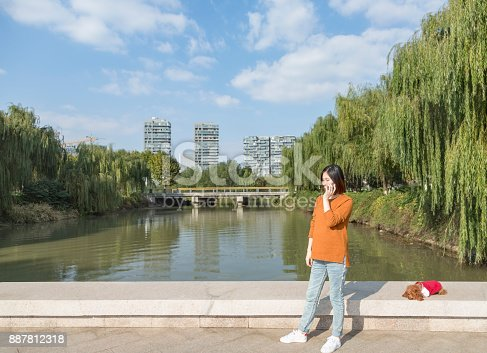 istock young asian pregnant woman talking on phone on park bridge 887812318