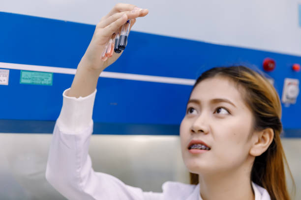 young asian researcher looking at the flask in the science laboratory. - medical technology стоковые фото и изображения