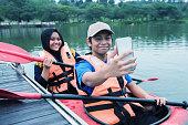 istock Young Asian siblings taking selfie on kayak at the lake 1255713906