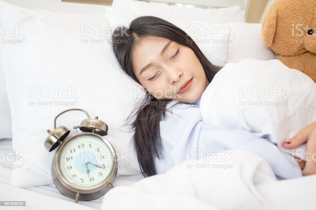 Young asian sleeping woman and alarm clock in bedroom at home, woman sleeping concept, 20s year old. stock photo