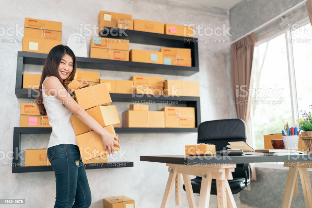 Young Asian small business owner carrying product boxes at home office, online marketing packaging and delivery scene, startup SME entrepreneur or freelance woman working at home concept stock photo