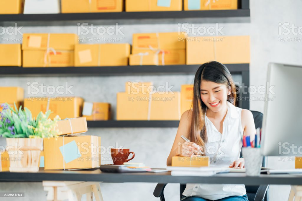 Young Asian small business owner working at home office, taking note on purchase orders. Online marketing packaging delivery, startup SME entrepreneur or freelance woman concept stock photo