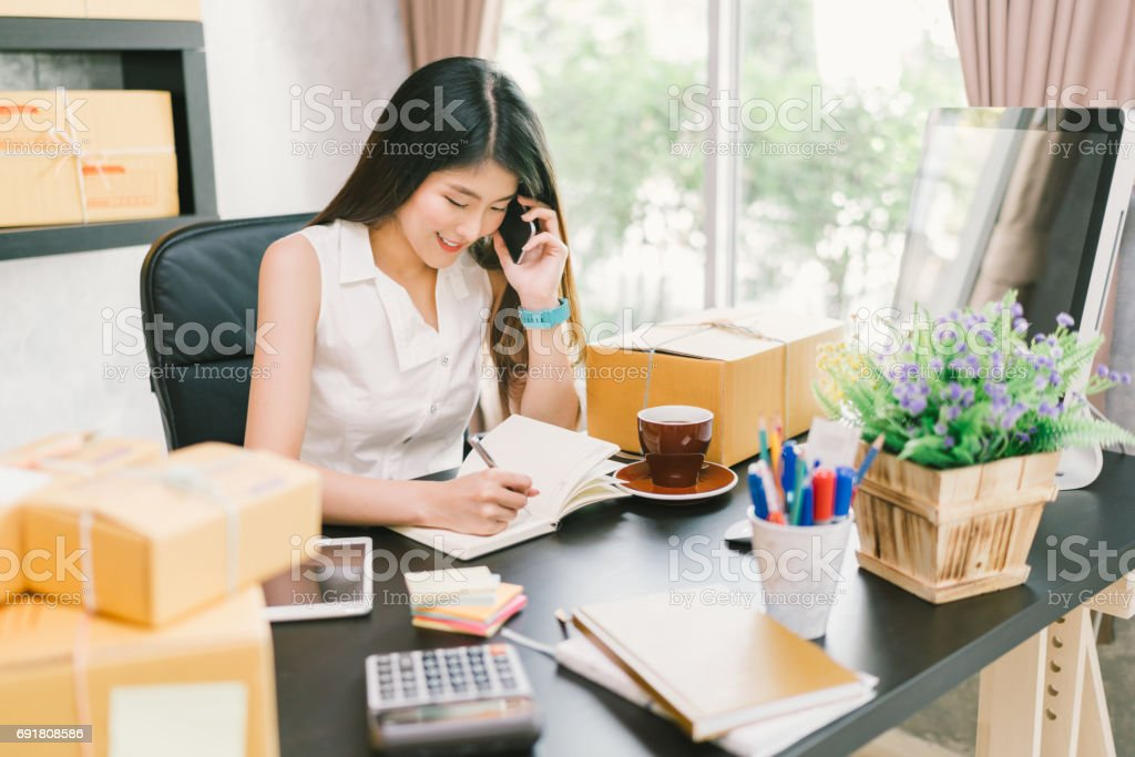 Young Asian small business owner working at home office, using mobile phone and taking note on purchase orders. Online marketing packaging delivery, startup SME entrepreneur or freelance woman concept stock photo