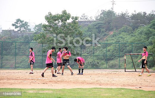 Jiangxi, China - March 11, 2012: Colour photograph of a group of young asian soccer football players, playing on an outdoor court in Ganzhou's Jiangxi province, China