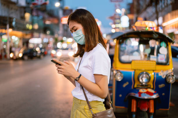 Young asian solo travel use moblie phone call taxi / bus transportation at chinatown road Bangkok thailand stock photo
