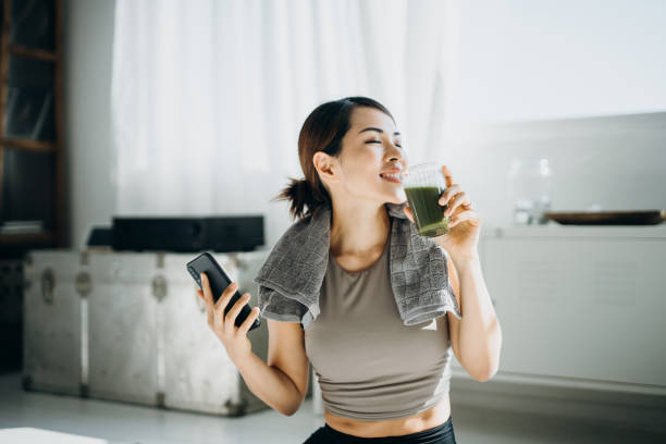 Young Asian sports woman resting and having green smoothie after exercising at home in the morning, using smartphone