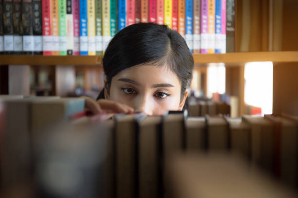 Young Asian student is searching for books in the library Young Asian student is searching for books in the library japanese school girl stock pictures, royalty-free photos & images