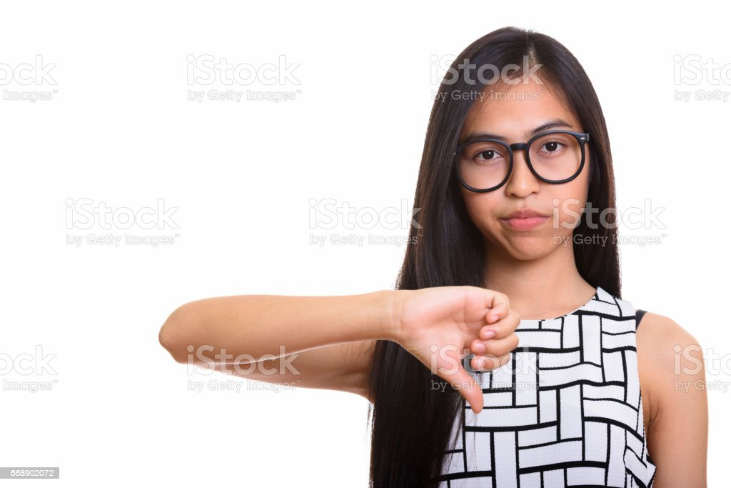 Young Asian Teenage Nerd Girl Giving Thumb Down Stock Photo