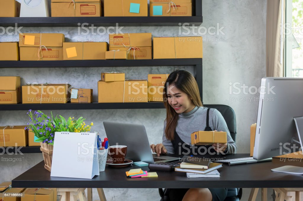 Young asian teenager owner business woman work at home for online shopping, checking order and prepaing package the product with office equipment, entrepreneur and alpha generation life style concept stock photo