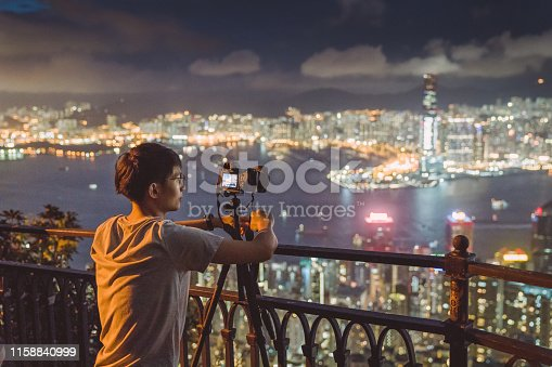 Young asian tourist adventure take photo of the HongKong cityscape Skyline at victoria peak the famaus tourist place in Hong kong