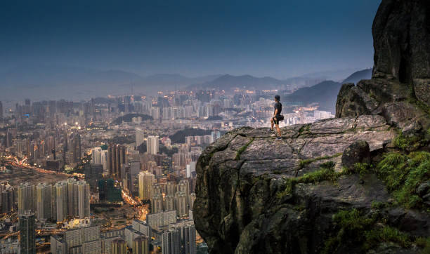 Young asian tourist adventure take photo of the HongKong cityscape Skyline at Suicide Cliff the famaus tourist place in Hong kong stock photo