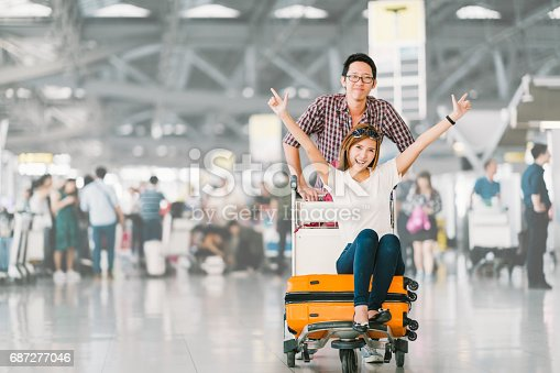 842907838 istock photo Young Asian tourist couple happy and excited together for the trip, girlfriend sitting and cheering on baggage trolley or luggage cart. Holiday vacation travelling abroad concept, with copy space 687277046