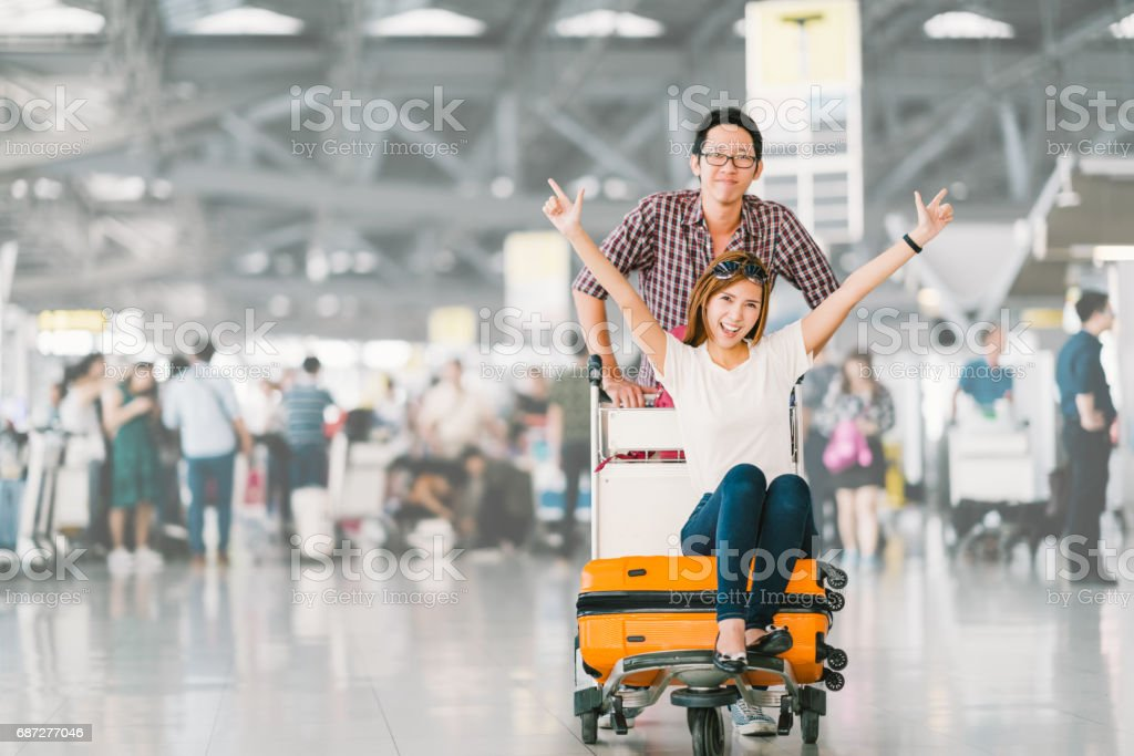 Pareja de turistas asiáticos jóvenes felices y emocionado para el viaje, novia sentado y animar en carro trolley o equipaje equipaje. Vacaciones viajar concepto en el extranjero, con espacio de copia - foto de stock