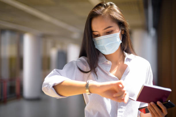 Young Asian tourist woman with mask checking time while holding passport at the airport stock photo