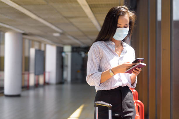 Young Asian tourist woman with mask using phone and holding passport at the airport stock photo