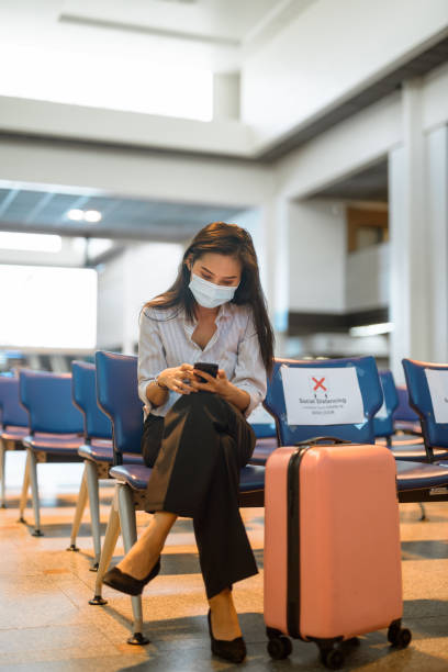 Young Asian tourist woman with mask using phone and sitting with distance at the airport stock photo