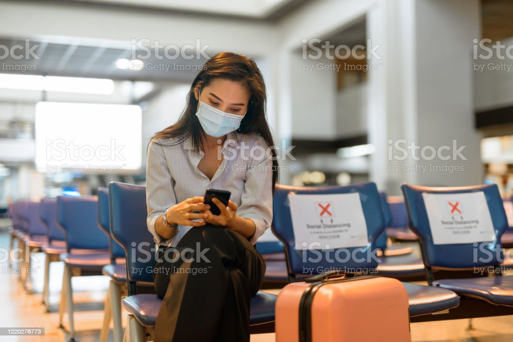 Young Asian tourist woman with mask using phone and sitting with distance at the airport Portrait of young Asian tourist woman with mask for protection from corona virus outbreak social distancing at the airport Adult Stock Photo