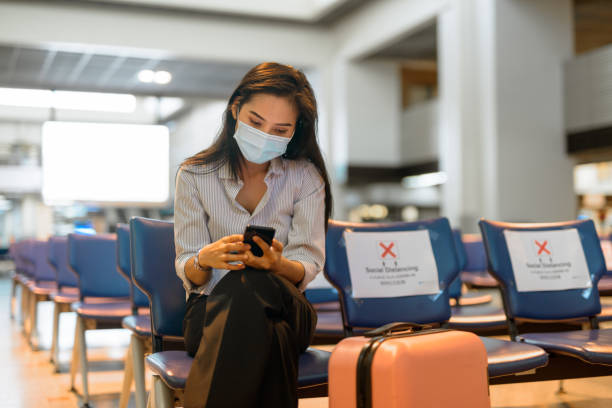 Young Asian tourist woman with mask using phone and sitting with distance at the airport Portrait of young Asian tourist woman with mask for protection from corona virus outbreak social distancing at the airport travel stock pictures, royalty-free photos & images