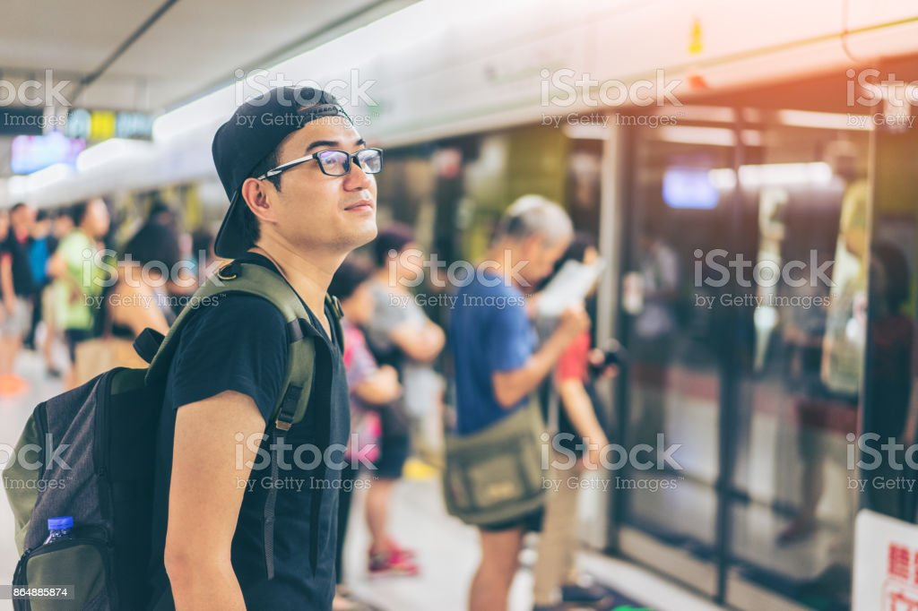 Young asian traveler waiting for transportation underground at Hong Kong MTR stock photo