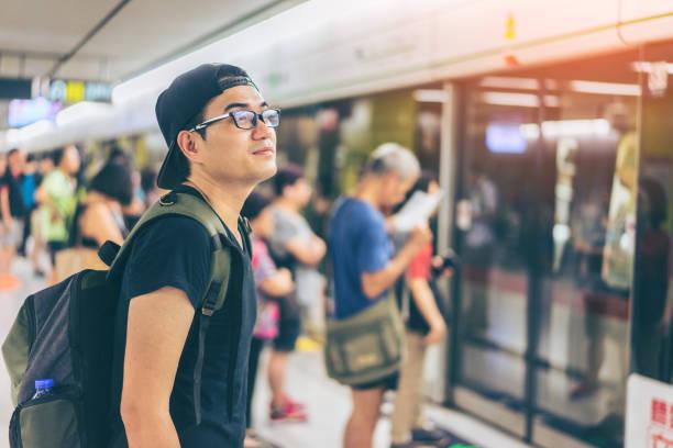 Young asian traveler waiting for transportation underground at Hong Kong MTR stock photo