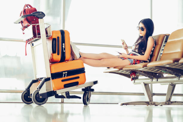 Young Asian traveler woman, university student sit using smartphone at airport, luggages and bag on trolley. Online flight check in mobile app, study abroad, or international tourism lifestyle concept stock photo