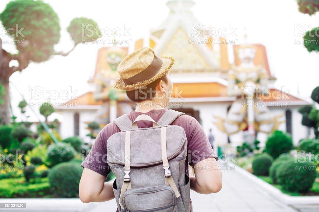 Young Asian traveling backpacker in Wat Arun in Bangkok, Thailand stock photo