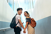 Young asian traveling couple holding hands and looking at camera