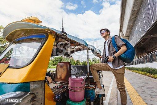 Young Asian traveller man standing with local Tuk Tuk taxi, Khonkaen city, Thailand