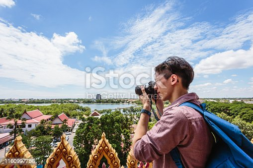 Young Asian traveller man travel taking pictures with camera at view from the top Wat Nong Waeng temple, Khonkaen, Thailand