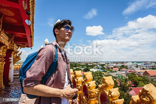 Young Asian traveller man travel with backpack at view from the top Wat Nong Waeng temple, Khonkaen, Thailand