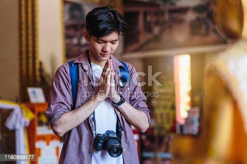 Young Asian traveller man travel with backpack respecting or pray at Wat Nong Waeng temple, Khonkaen, Thailand
