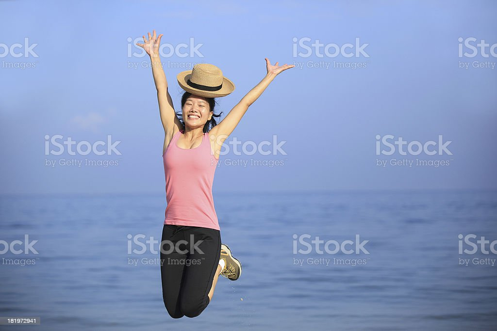 young asian vacation woman jumping on beach royalty-free stock photo