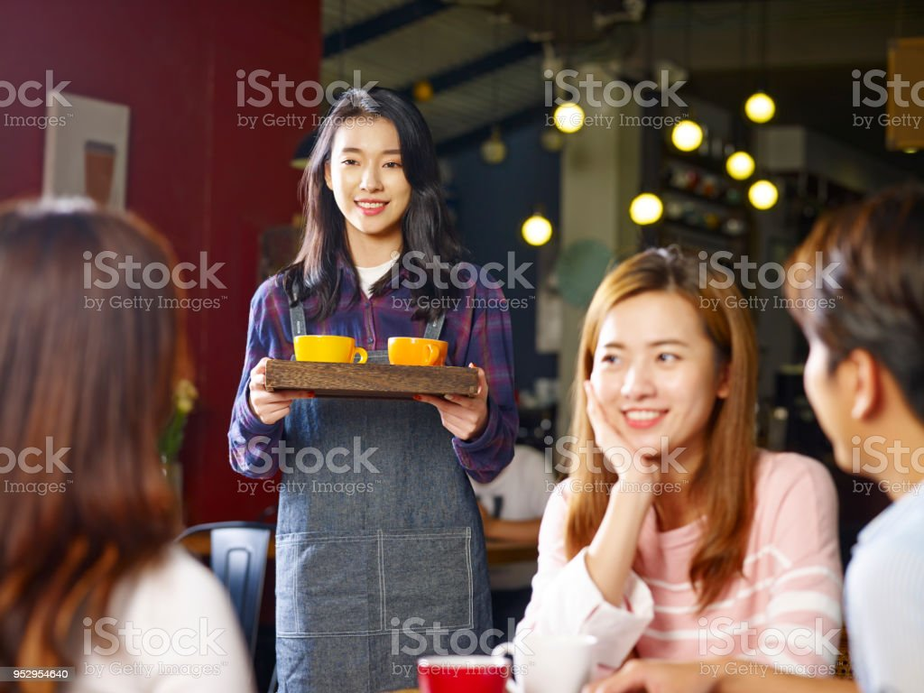 Young Asian Waitress Bringing Drinks To Customers Stock