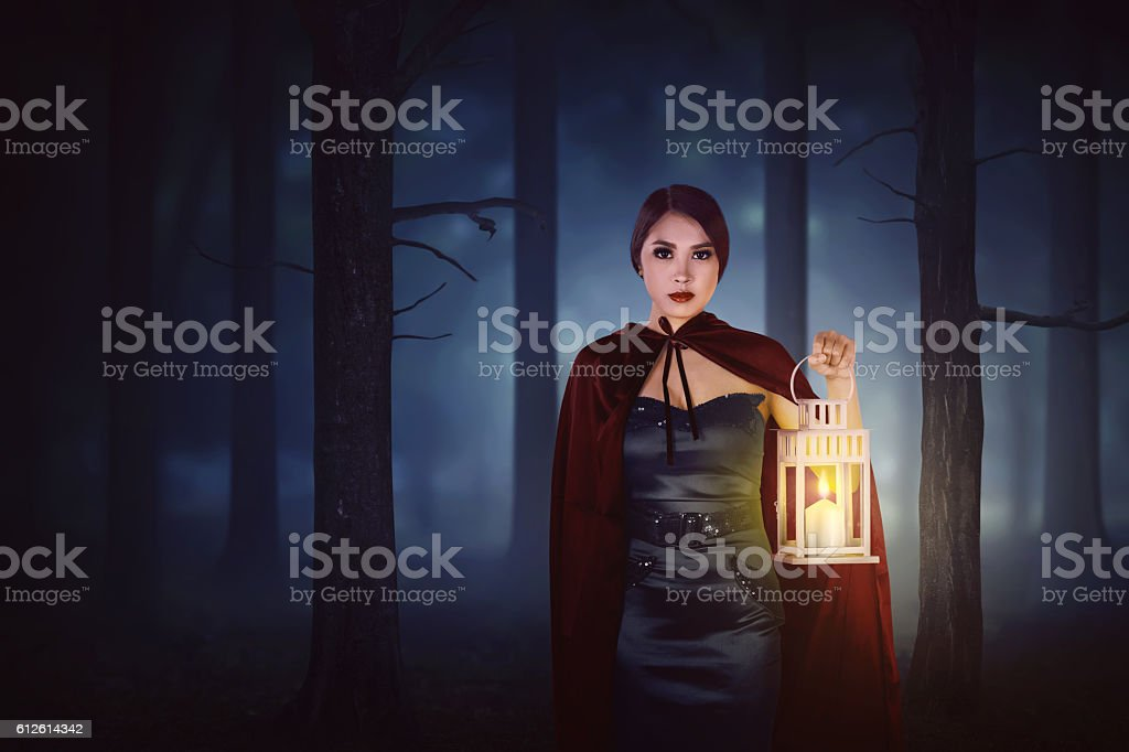 Young asian witch woman with red cloak walking in forest stock photo