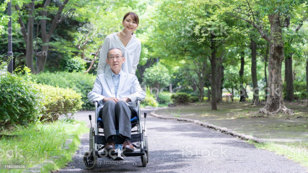 Young Asian Woman And Old Asian Man With Wheelchair In