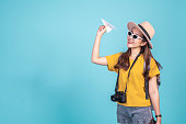Young Asian woman backpacker traveler holding paper plane over blue background for travel concept