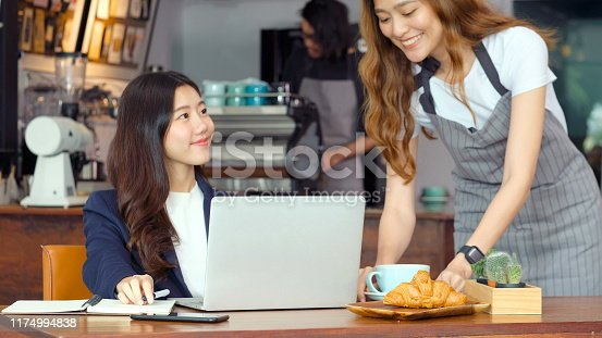 1066358064istockphoto Young asian woman barista serving a coffee cup with smiling to businesswoman customer while she working on laptop computer at cafe coffee shop background 1174994838