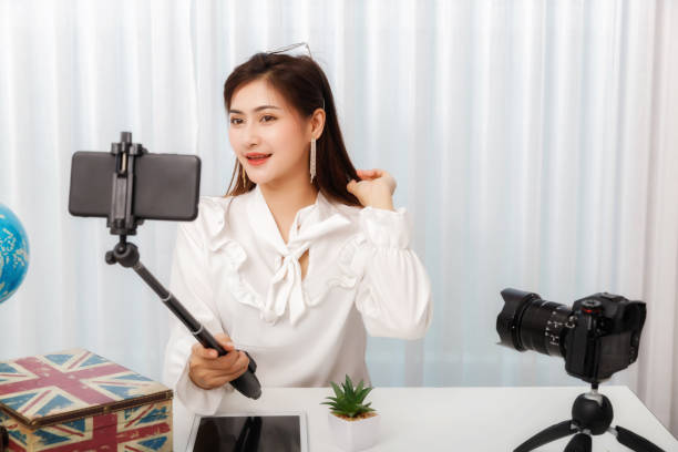 young asian woman blogger selfie herself with smart phone while recording vlog video live streaming. blogger and vlogger online influencer on social media concept. - woman chat video mobile phone foto e immagini stock
