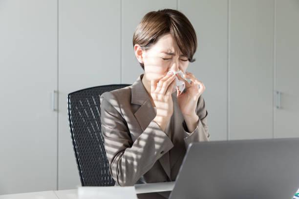 若いアジアの女性は、彼女の鼻を吹きます。鼻の炎症。花粉症。 - くしゃみ 日本人 ストックフォトと画像