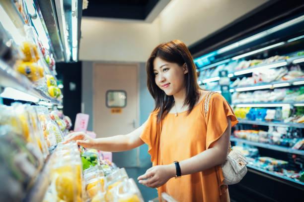 Young Asian woman choosing fresh organic fruits in supermarket. stock photo