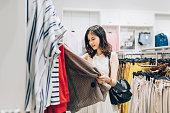 衣料品店で新しい服を選ぶアジアの若い女性。