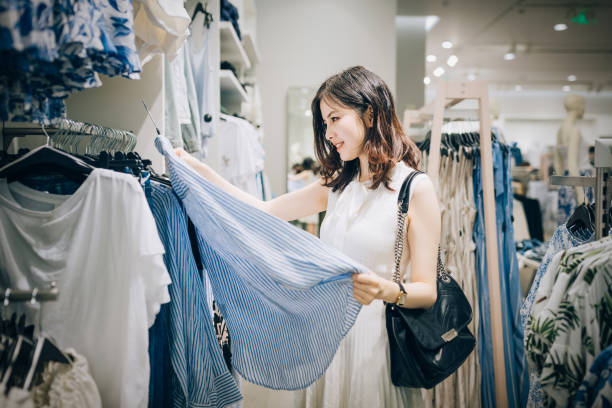 Young Asian woman choosing new clothes in the clothing store. stock photo