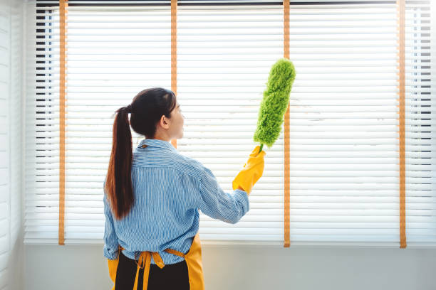 Young asian woman cleaning house wiping dust using Feather broom and duster while cleaning on window House keeping concept stock photo