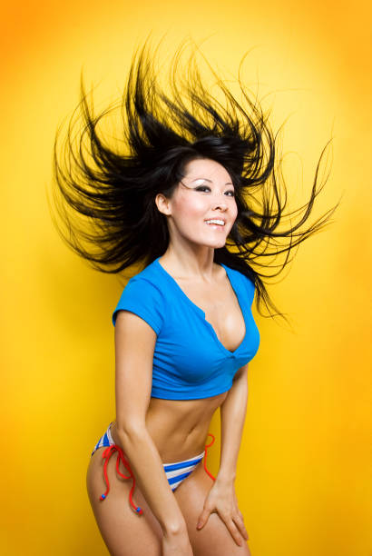Young Asian Woman Dancing, Isolated on Yellow stock photo