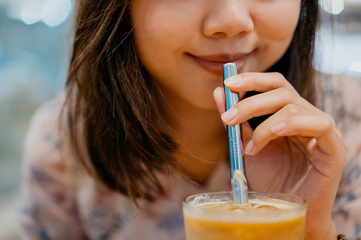 Young asian woman drink coffee using metal straw. Reducing paper or plastic waste.