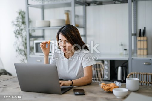 Young Asian woman drinking coffee and having healthy snacks while working from home using laptop computer in the living room