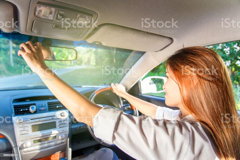 Motorista de jovem mulher asiática ajustando seu espelho retrovisor no carro. - foto de acervo