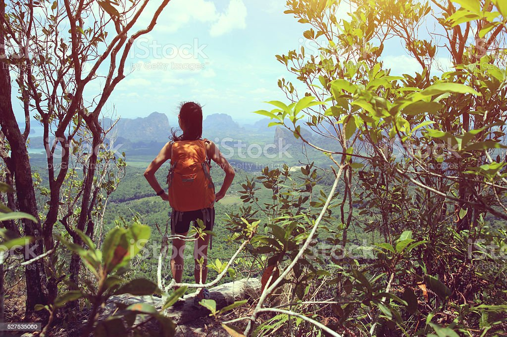 young asian woman enjoy the view at mountain peak cliff stock photo