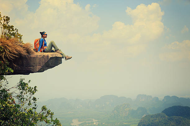 young asian woman enjoy the view at  mountain peak stock photo
